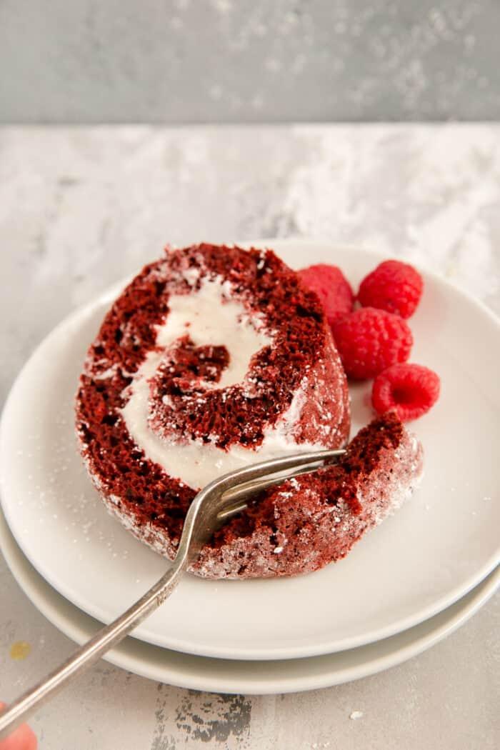 fork digging into a slice of red velvet cake roll
