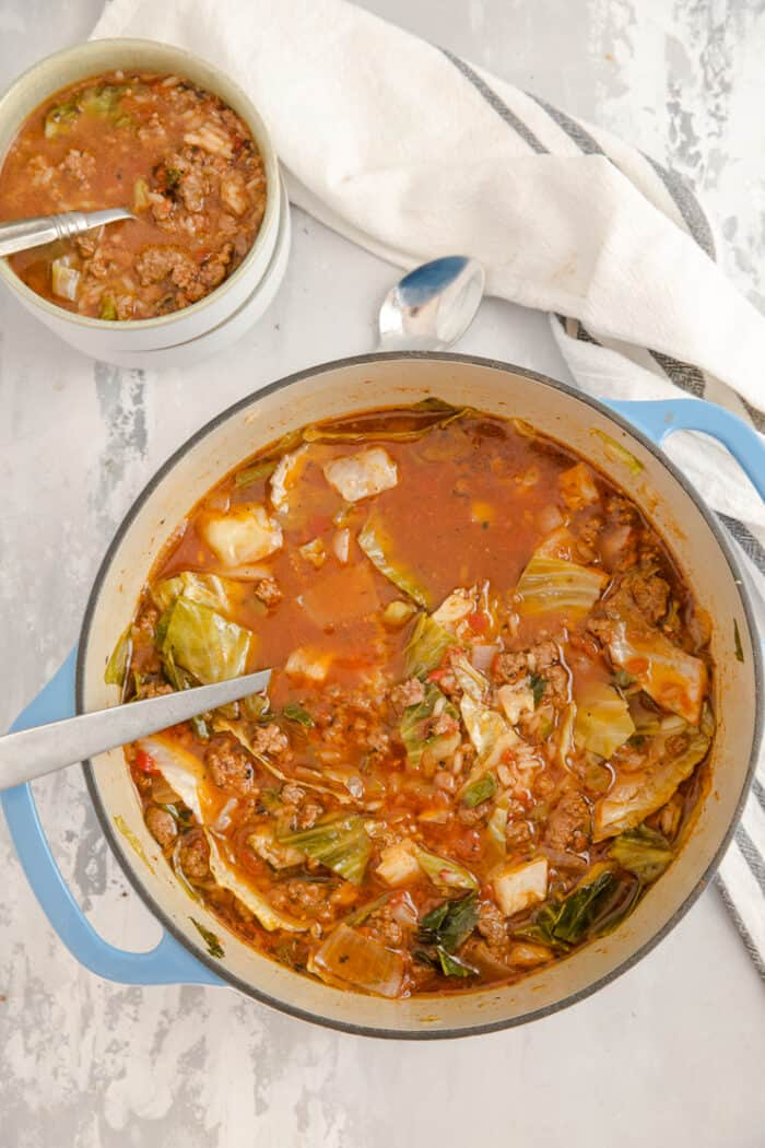 cabbage roll soup in a dutch oven with a bowl on the side
