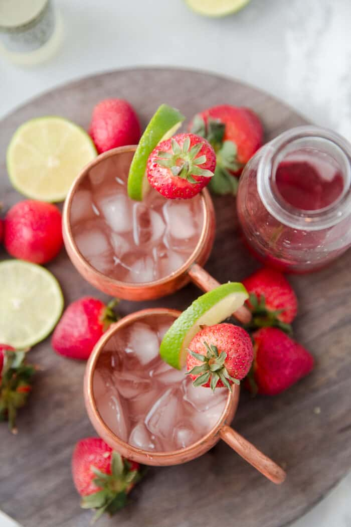two moscow mules with strawberries and limes