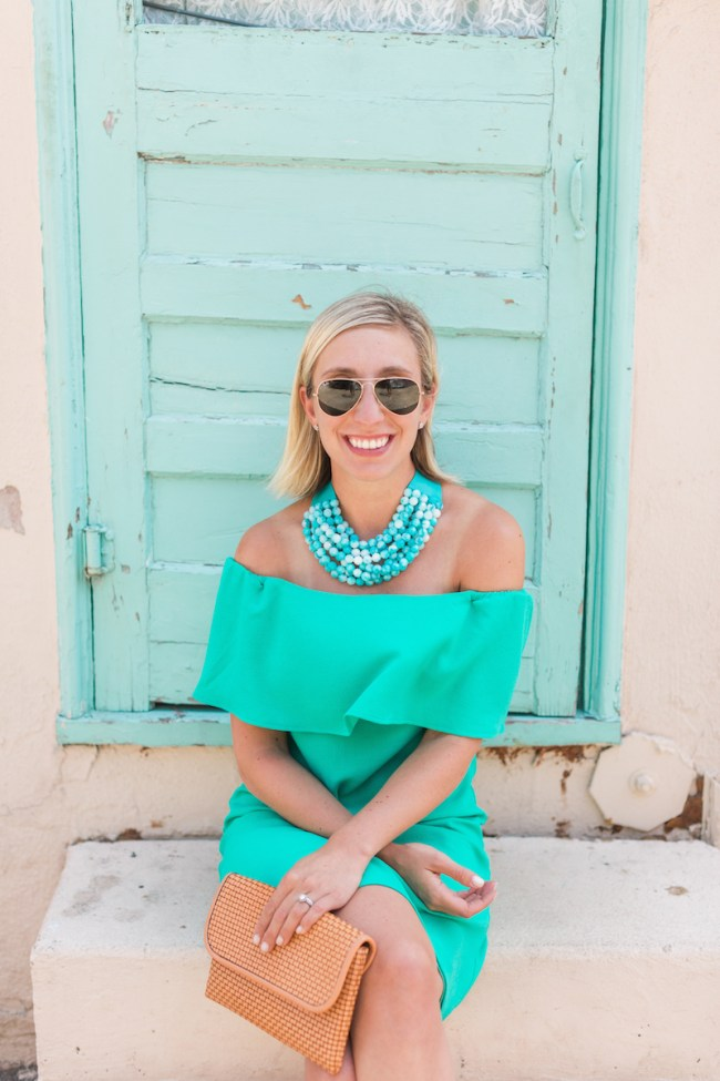 Julia Dzafic wearing an off shoulder green dress and oversized necklace