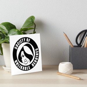 Desk with potted plant, ball of twine, pencil cup, and art print of Society of Unlikable Heroines logo