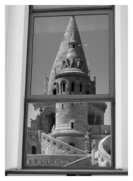 Modern building window reflecting Fisherman's Bastion in Budapest