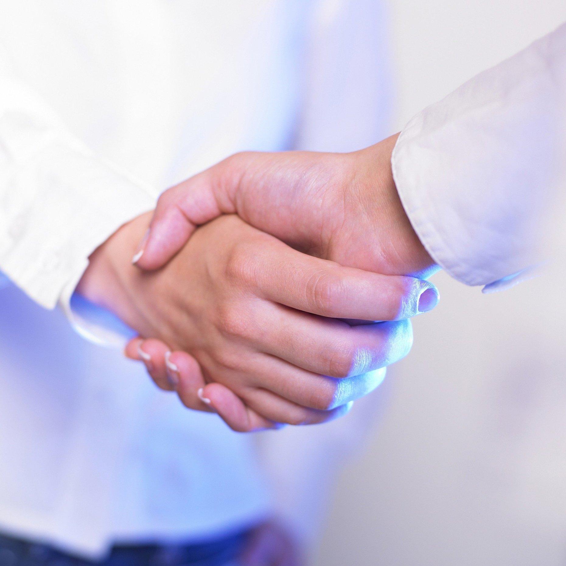 Zwei Personen im weißen Kittel geben sich die Hand.
