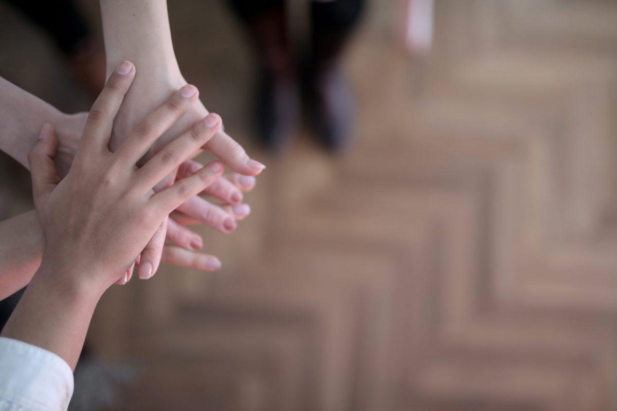 Drei Hände von Kindern sowie älteren Personen liegen übereinander, um Zusammenhalt zu symbolisieren. Im Hintergrund sind Beine in einer schwarzen Hose sowie ein dunkler Holzfußboden zu erkennen.