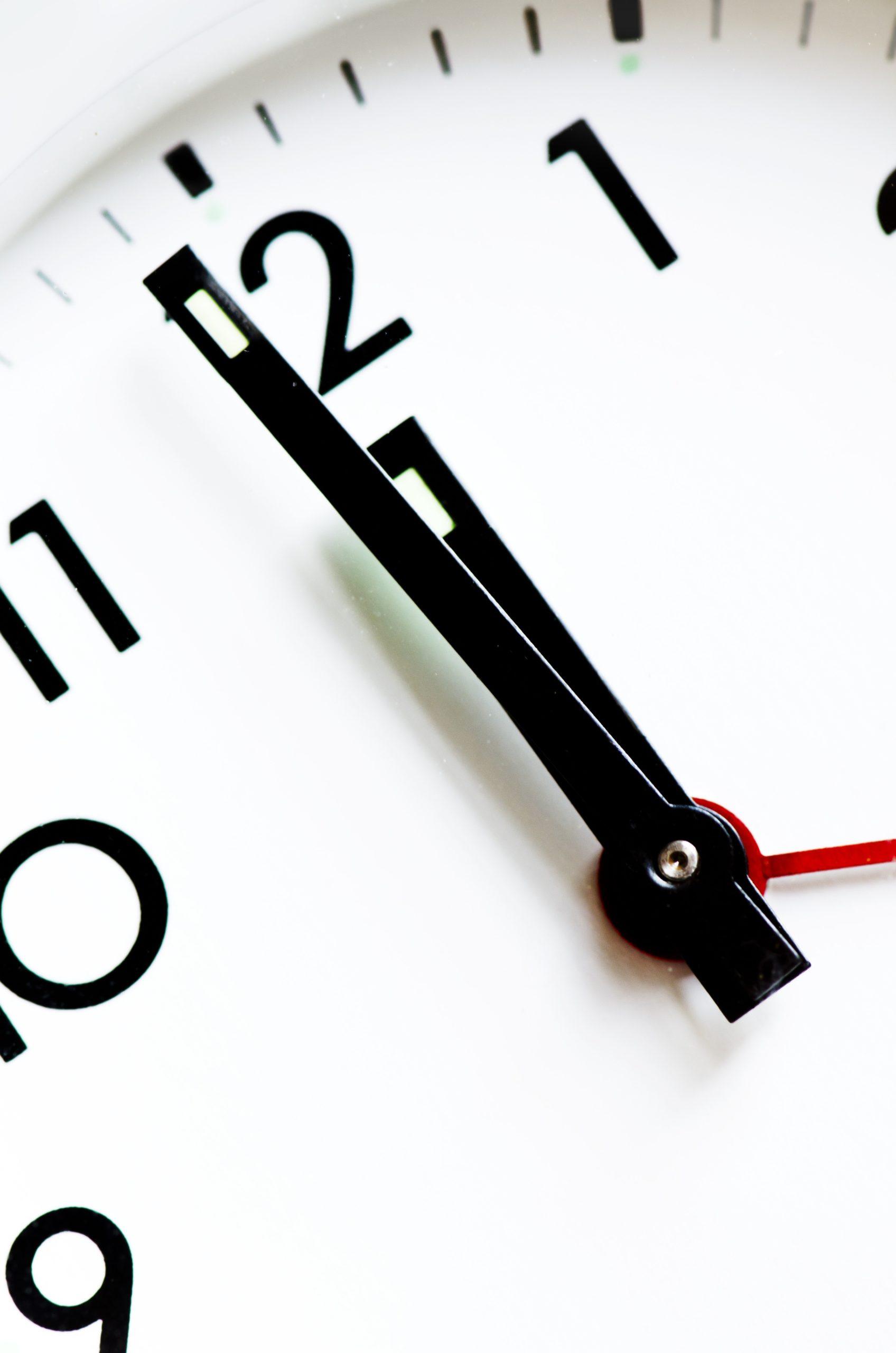 Nahaufnahme des Ziffernblattes eines Weckers. Die Zeiger stehen auf kurz vor zwölf Uhr.