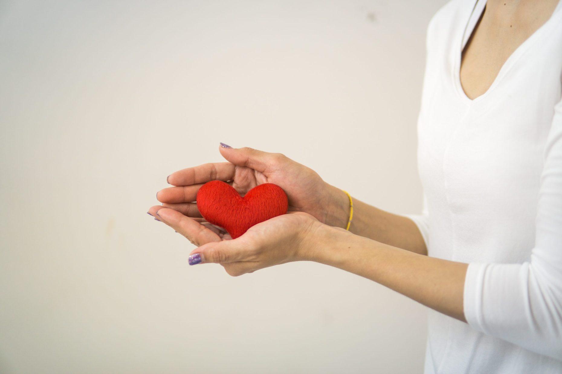 Frau mit weißem Oberteil hält ein rotes Herz aus Stoff in ihren Händen.