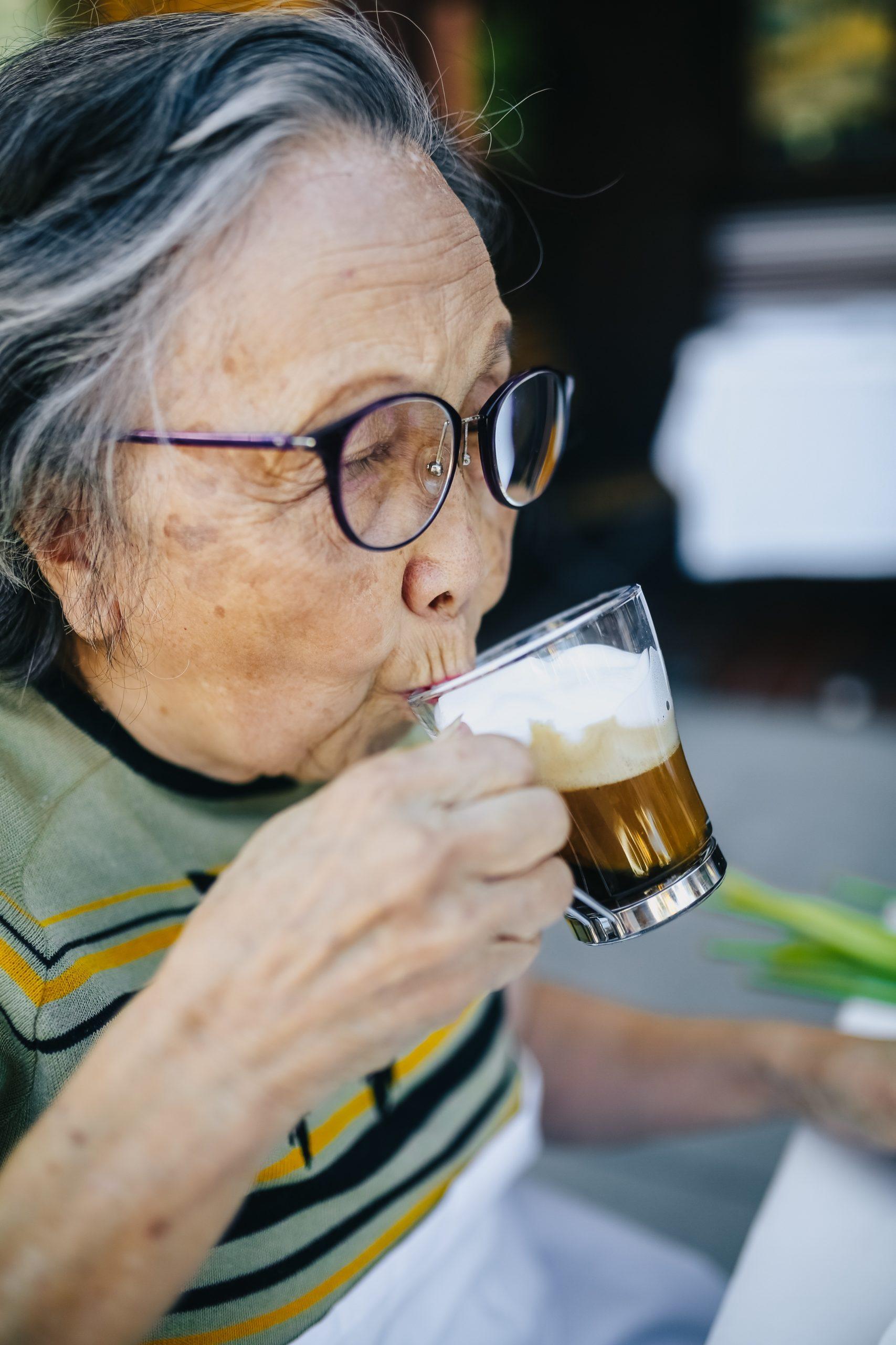 Seniorin mit großer Hornbrille trinkt Kaffee aus einem Glas.