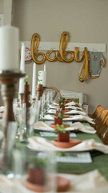 a table setting for a baby shower with a balloon that spells out baby