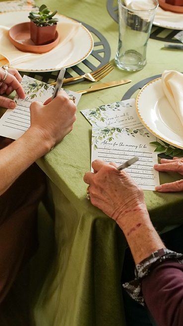 close up of people writing stuff down at a baby shower