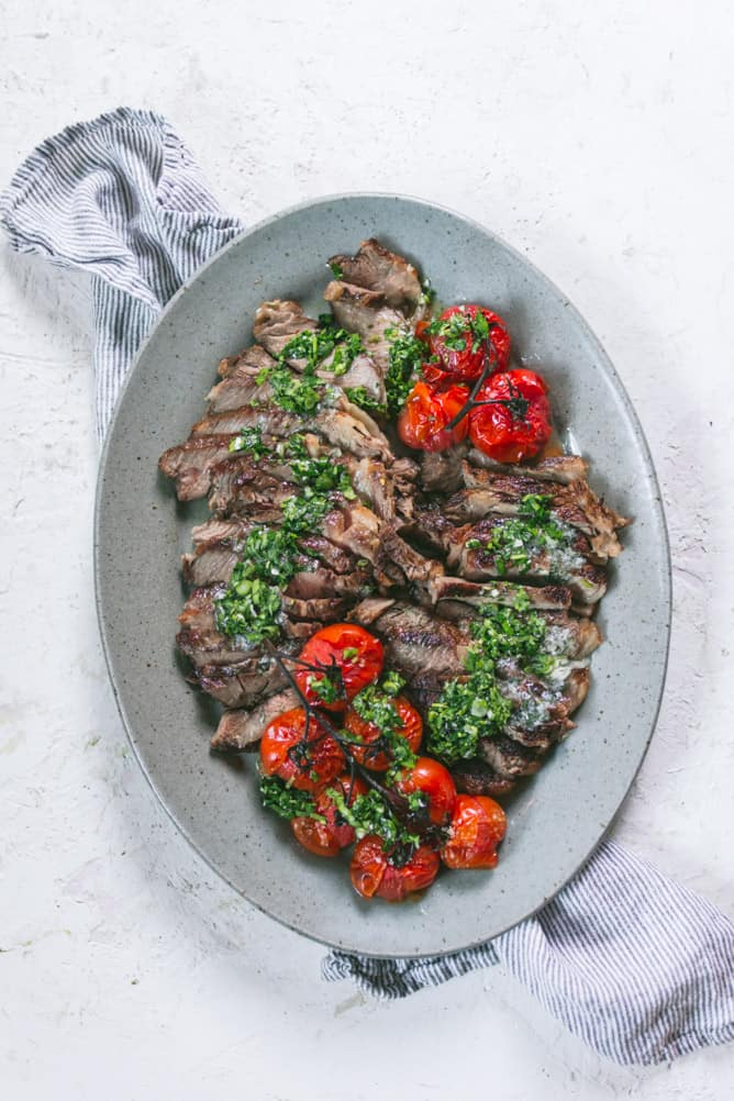 easy rib-eye steak cooked in the oven with chimichurri sauce and roasted tomatoes