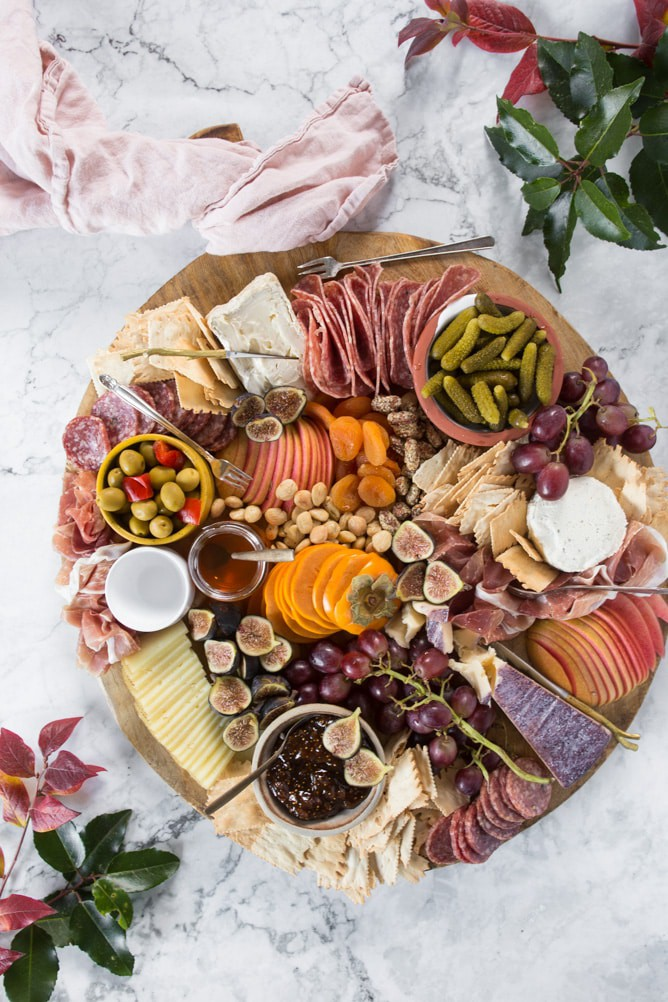 charcuterie board filled with meats, cheeses, fruits and crackers.