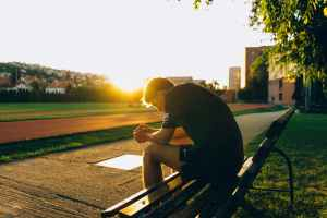 man sitting on bench near track field while sun is setting