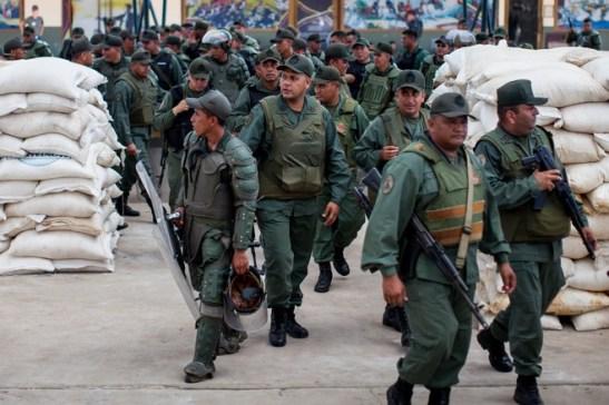 Binh lính Vệ binh Quốc gia canh giữ thực phẩm bị tịch thu từ những người tìm cách bán cao giá hơn giá do chính phủ ấn định. (Miguel Gutiérrez / The Wall Street Journal)