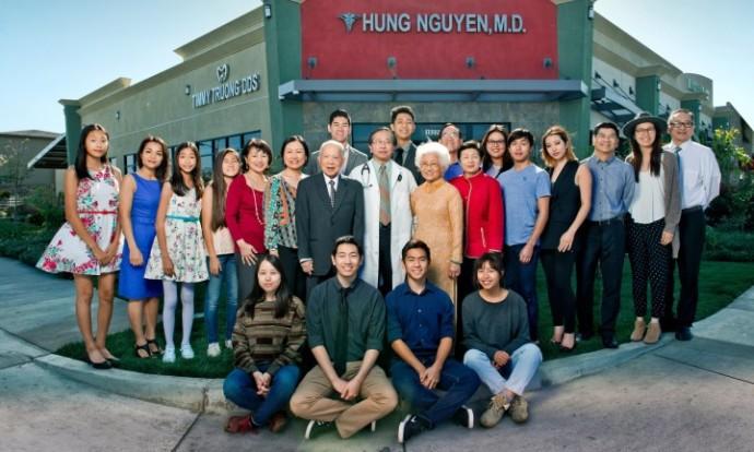 Bác sĩ Hung Nguyen (trên, giữa), một trong những thuyền nhân được tàu MV Wellpark cứu, cùng với gia đình bên ngoài trung tâm y khoa của ông ở Quận Cam, California. (Ảnh: Barry J Holmes / The Observer)