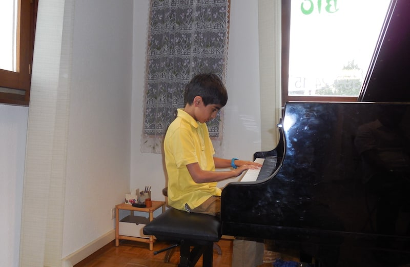 Pedraam playing a grand piano in his bedroom in an apartment in Geneva