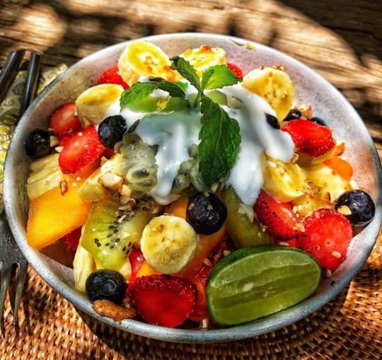 fruit bowl, ovocná misa s jahodami, banánom, kiwi, čučoriedkami a limetkou, preliate bielym jogurtom, ozdobené kúskom mäty, Bali