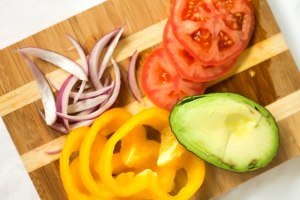tomato slices, yellow pepper rings, avocado, and red onion on a wooden cutting board