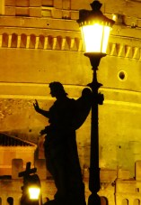 An angel besides a streetlamp is thrown into sharp contrast by all the light.