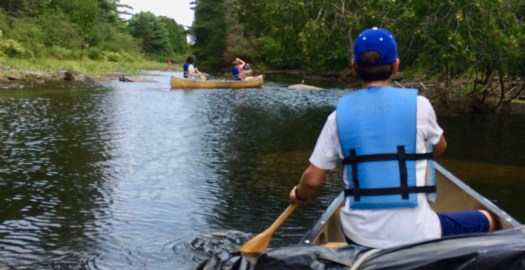 Canoeing on a river. Up ahead are two more canoes. One is hardly distinguishable.