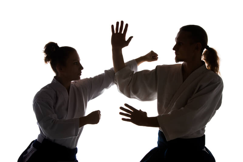 Male and Female Aikdo martial artists throwing punch