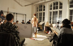 una modella che posa nuda di fronte a una classe di studenti di disegno.