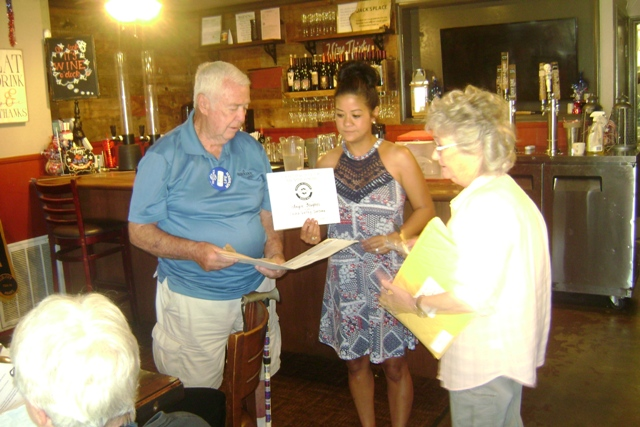 Joh Seymor presents new member, Angie Hughes, her membership packet.