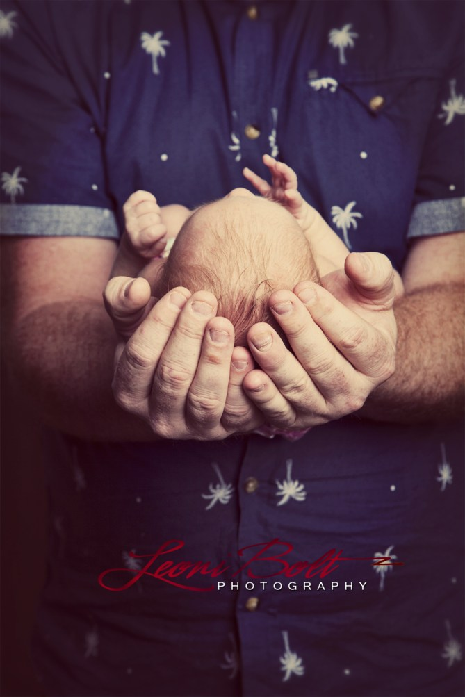 newborns head in dad's hands