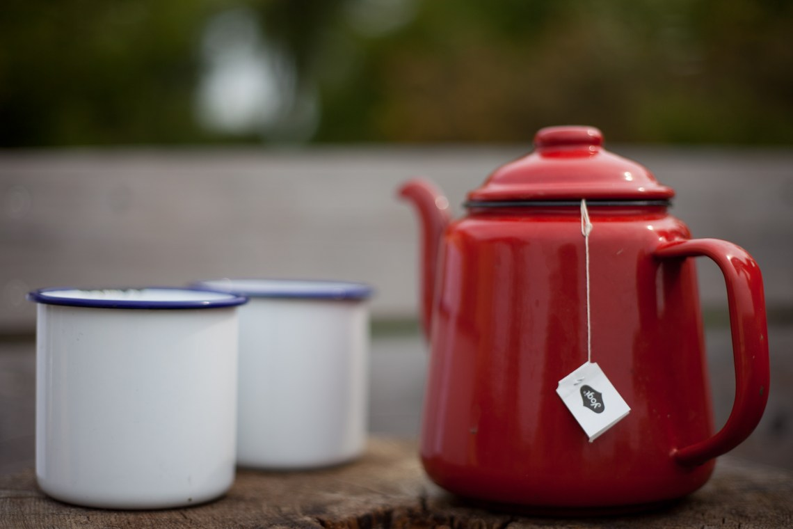 Red enamel teapot and enamel cups. By Leonie Wise