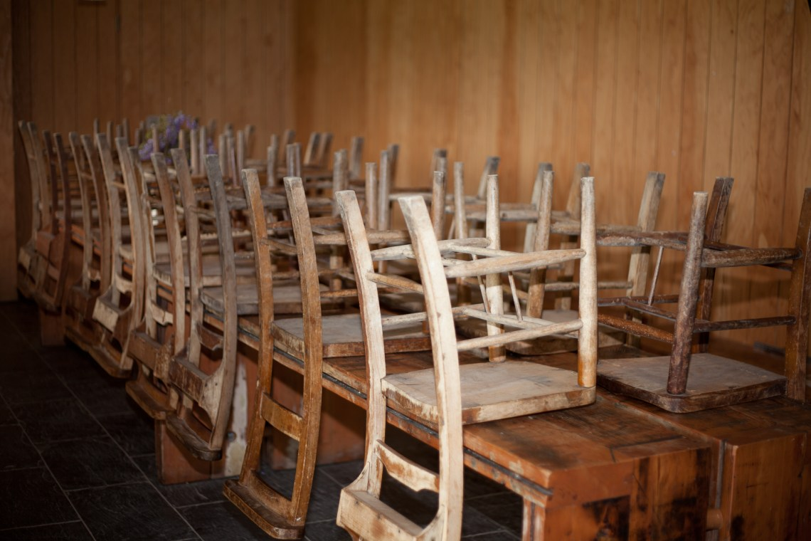 Chairs upturned on tables. By Leonie Wise
