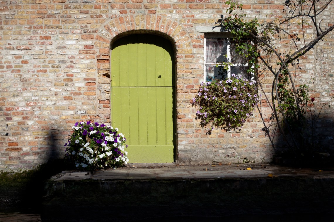 green door on the canal in brugge. by leonie wise
