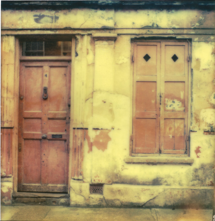 polaroid of a pink door and shutter. copyright leonie wise