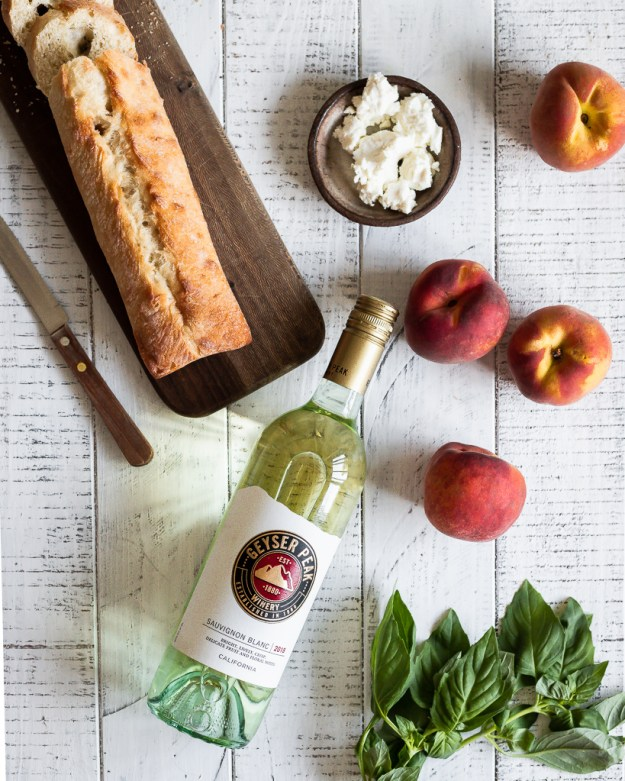 ingredients for grilled peach bruschetta on a white wood surface and a bottle of sauvignon blanc