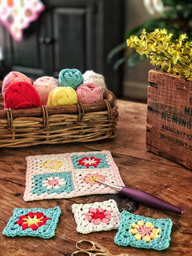 Turquoise, red, yellow, white, and pink granny squares on a rustic table.