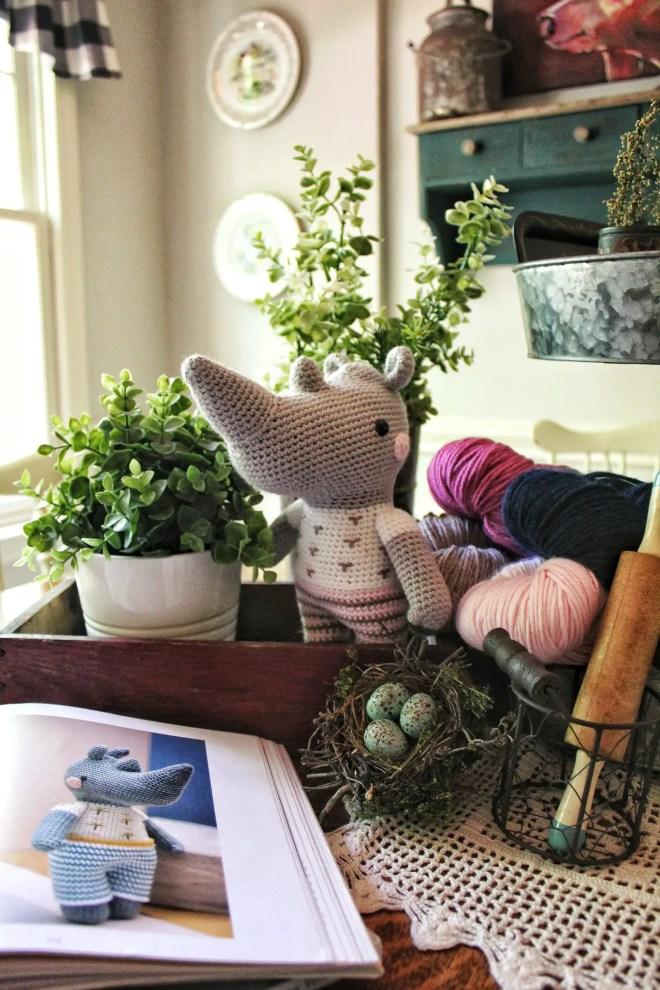 Amigurumi rhinoceros amongst plants, books, and colorful yarn!