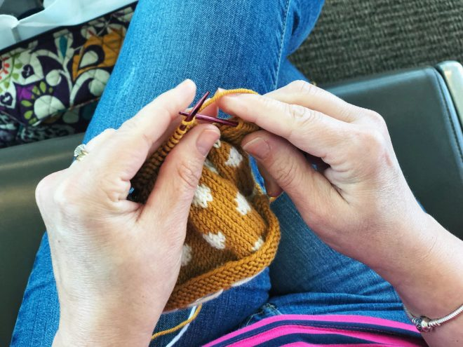 Knitting a mustard yellow and white polka dot dress in the airport.