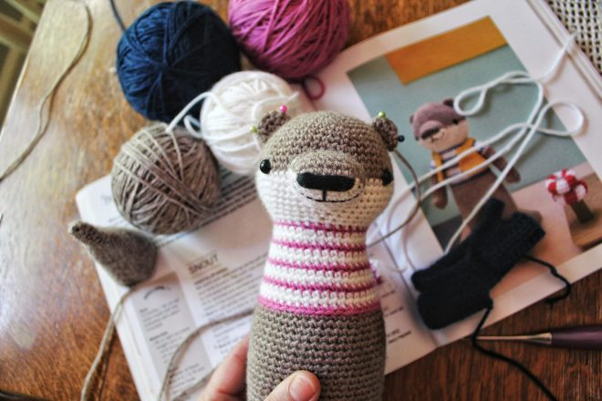Amigurumi otter with pinned on ears.