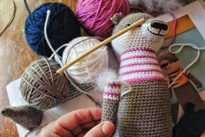 Amigurumi otter arm being stuffed with Poly-fil.