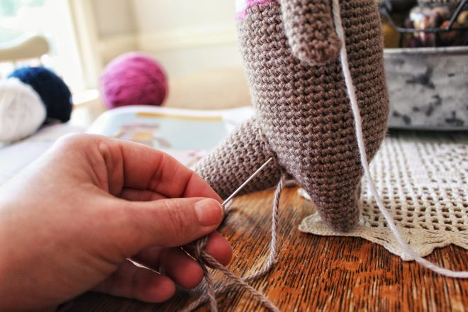 Sewing on tail of amigurumi otter.