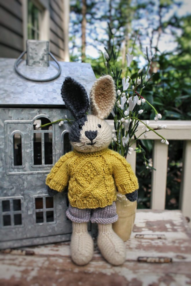 Hand knit rabbit with yellow cable knit sweater.