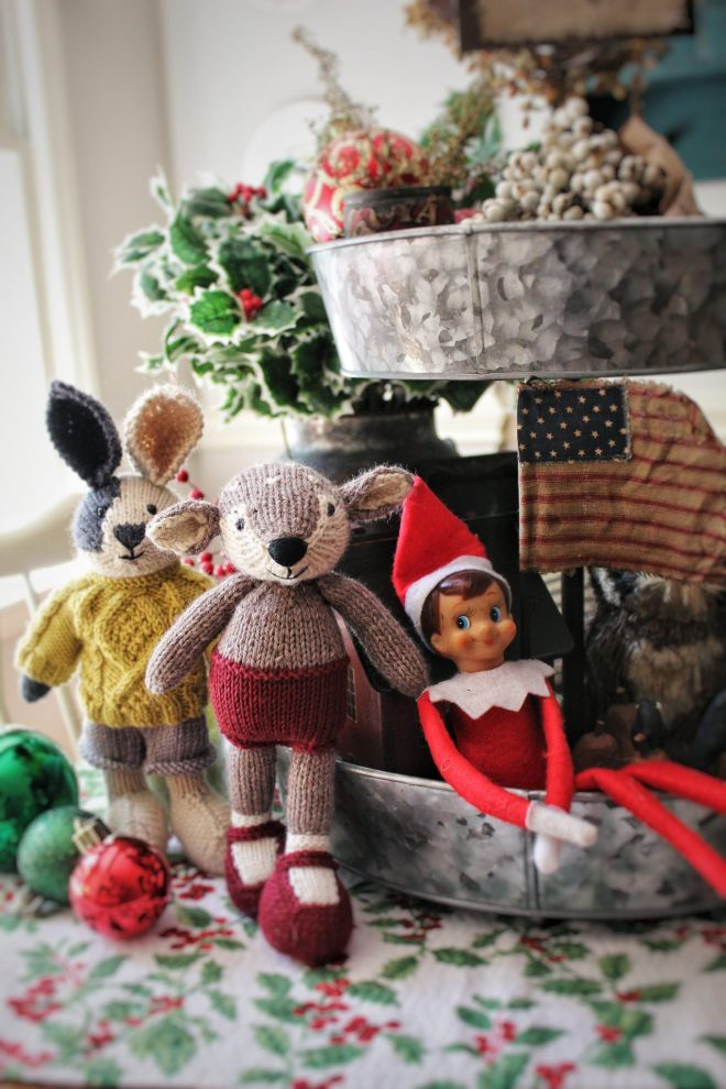 Knitted deer and rabbit toy with Elf on the Shelf. American flag and Christmas ornaments all on the same table.