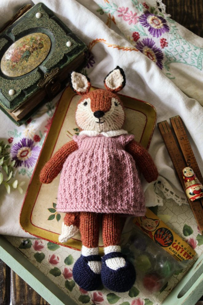 Knitted toy fox with rose colored textured dress