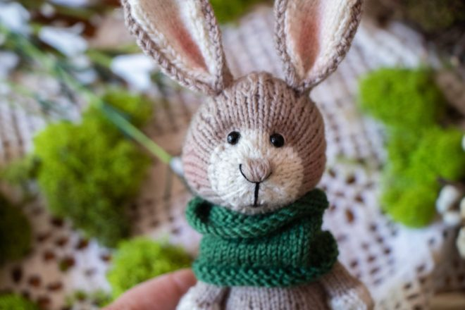 Knitted bunny in a moss green scarf.