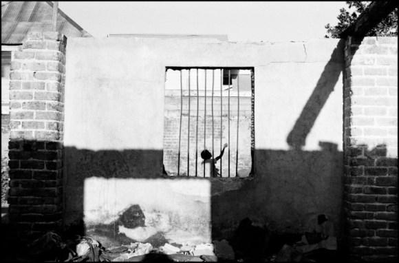 Un enfant qui joue dans une maison dont le toit est détruit