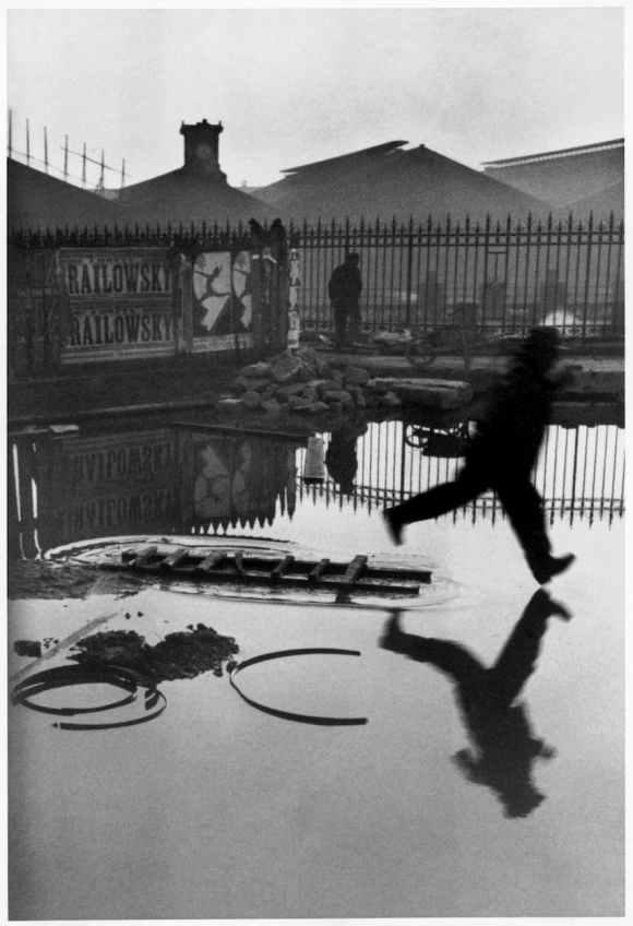 cartier-bresson : homme saute flaque d'eau