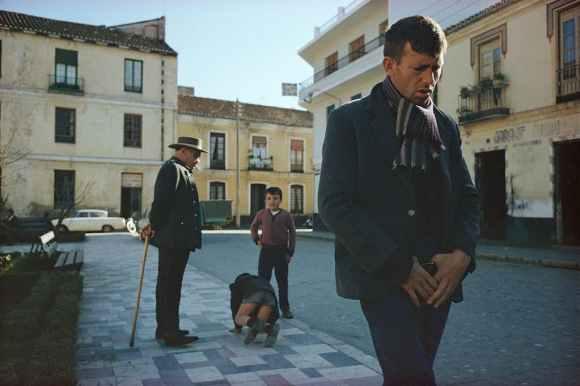 un homme marche, deux enfants jouent, un vieil homme les regardent
