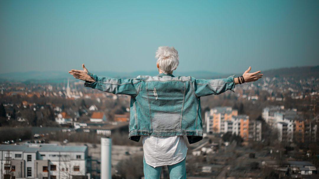 osoba z białymi włosami stojąca z rozpostartymi ramionami patrząc na panoramę miasta przed sobą
