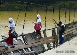 Des-enfants-prennent-un-pont-suspendu-en-destruction-Lebak-Indonesie. (Ph:Dr)