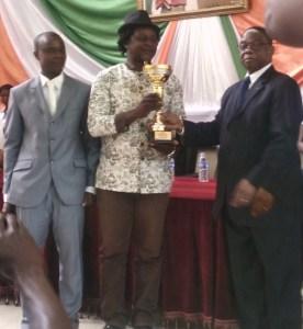 Le Guide-Evêque ivoirien du MRI tenant le trophée du prophète Raël.