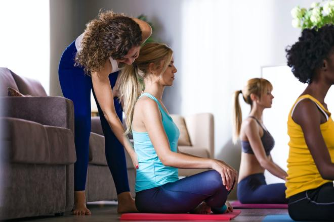 Pretty yoga instructor helping her student in a yoga session at