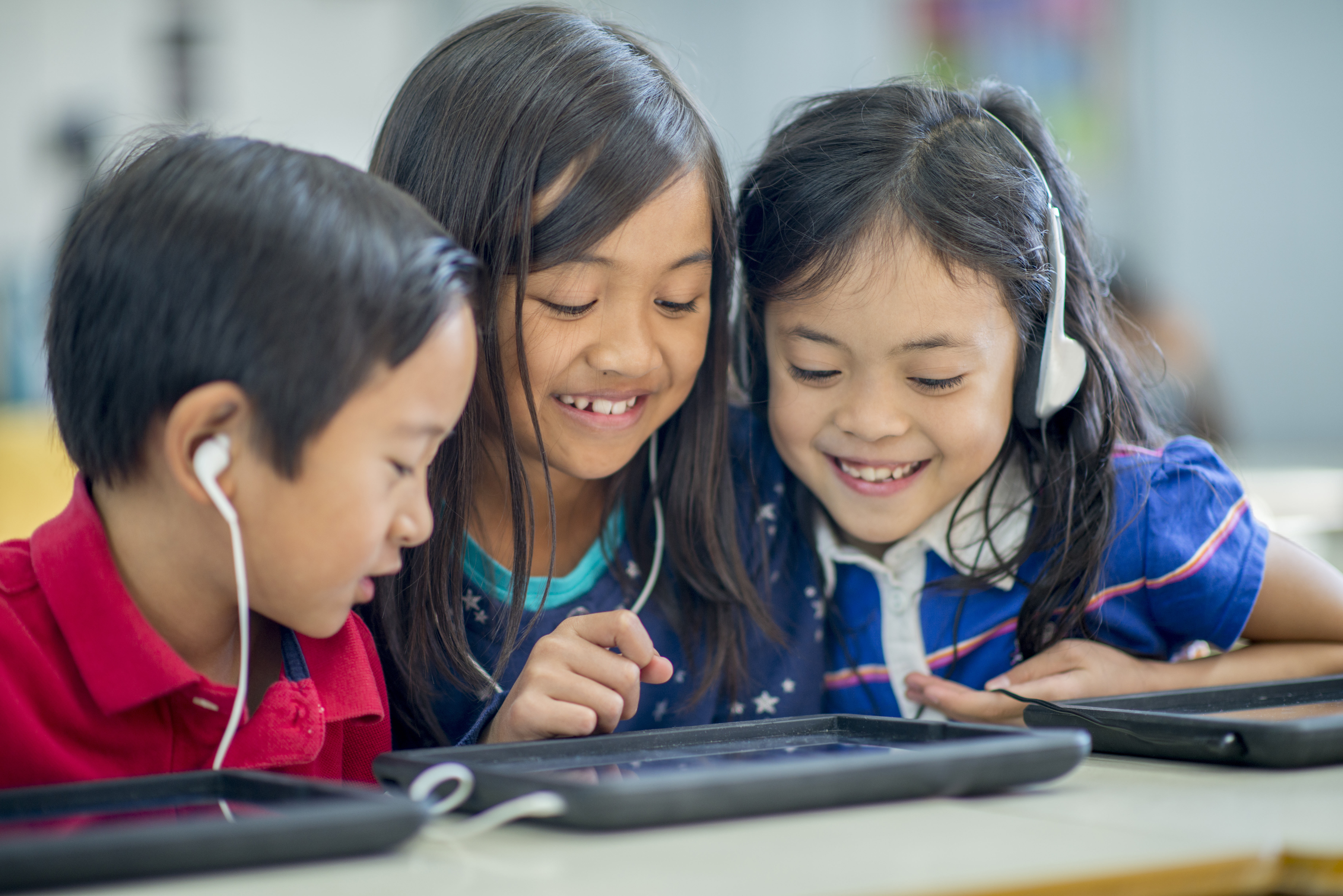 Children using tablet to view eBooks with audio